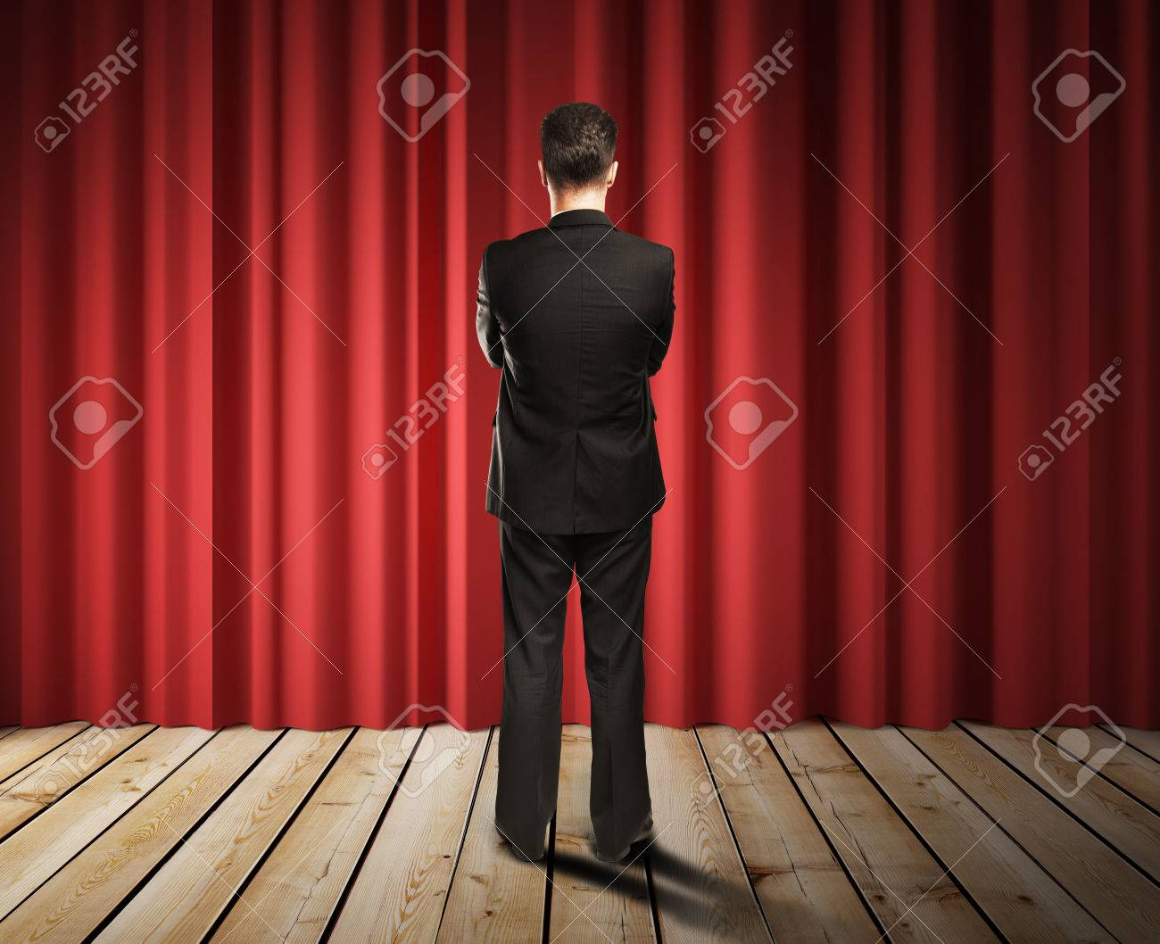 businessman looking to red curtains in room Stock Photo - 29806448
