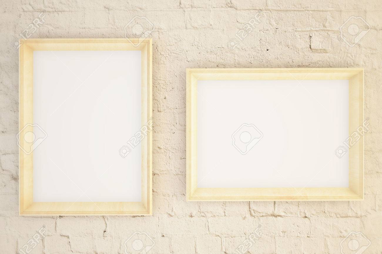 Two Blank Picture Frames Hanging On A Beige Brick Wall Mock Stock
