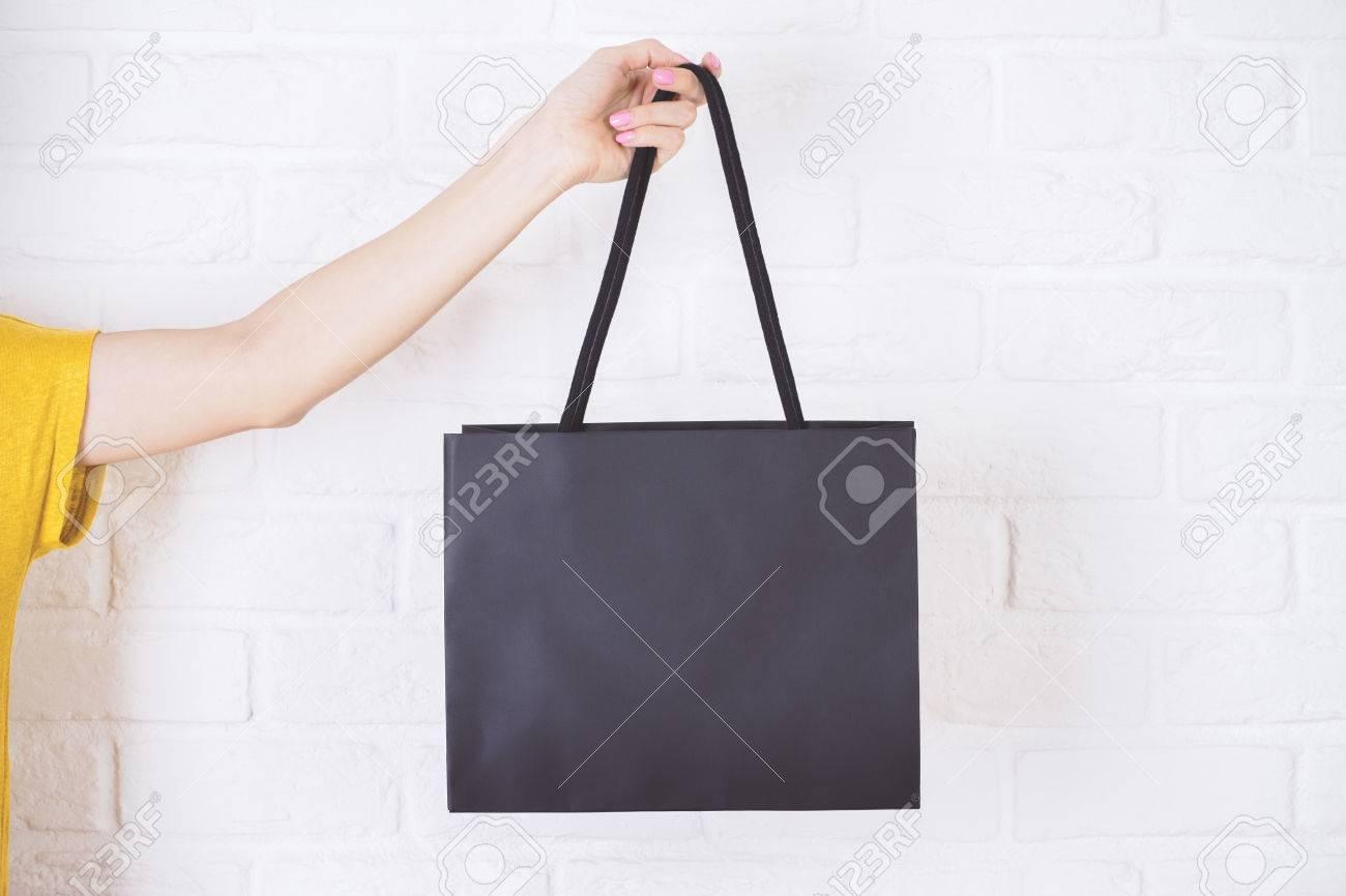 Closeup of female hand holding black shopping bag on white brick background. - 54889720