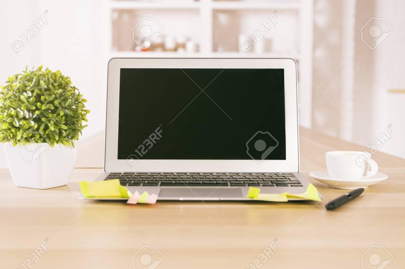 Bureau avec ordinateur portable noir vide tasse de plantes et de
