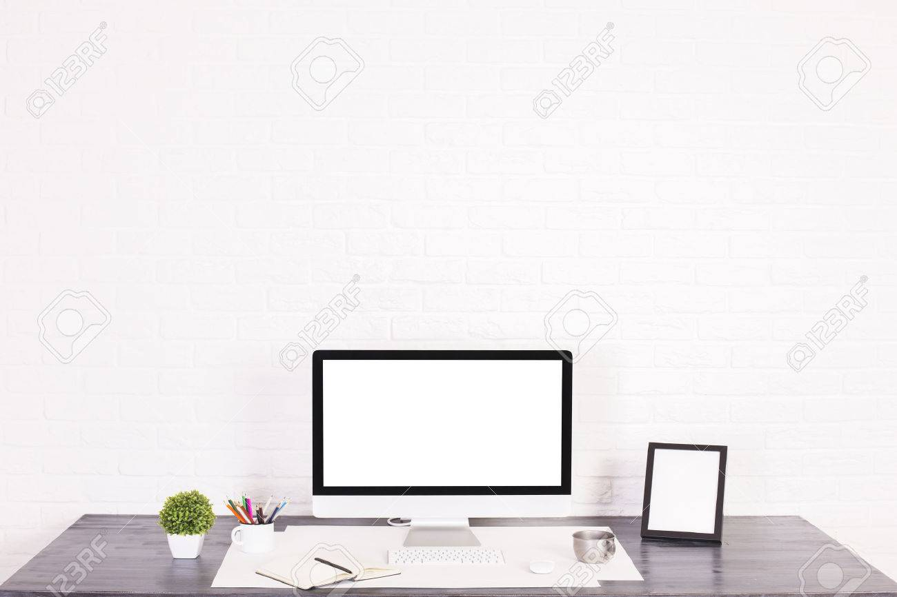 designer desktop with blank white computer monitor picture frame