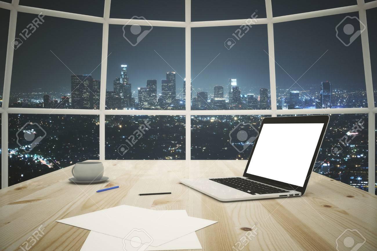 Gros plan du bureau en bois clair avec un ordinateur portable