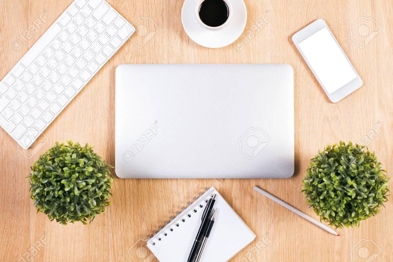 Ordinateur portable fermé sur le bureau en bois avec clavier