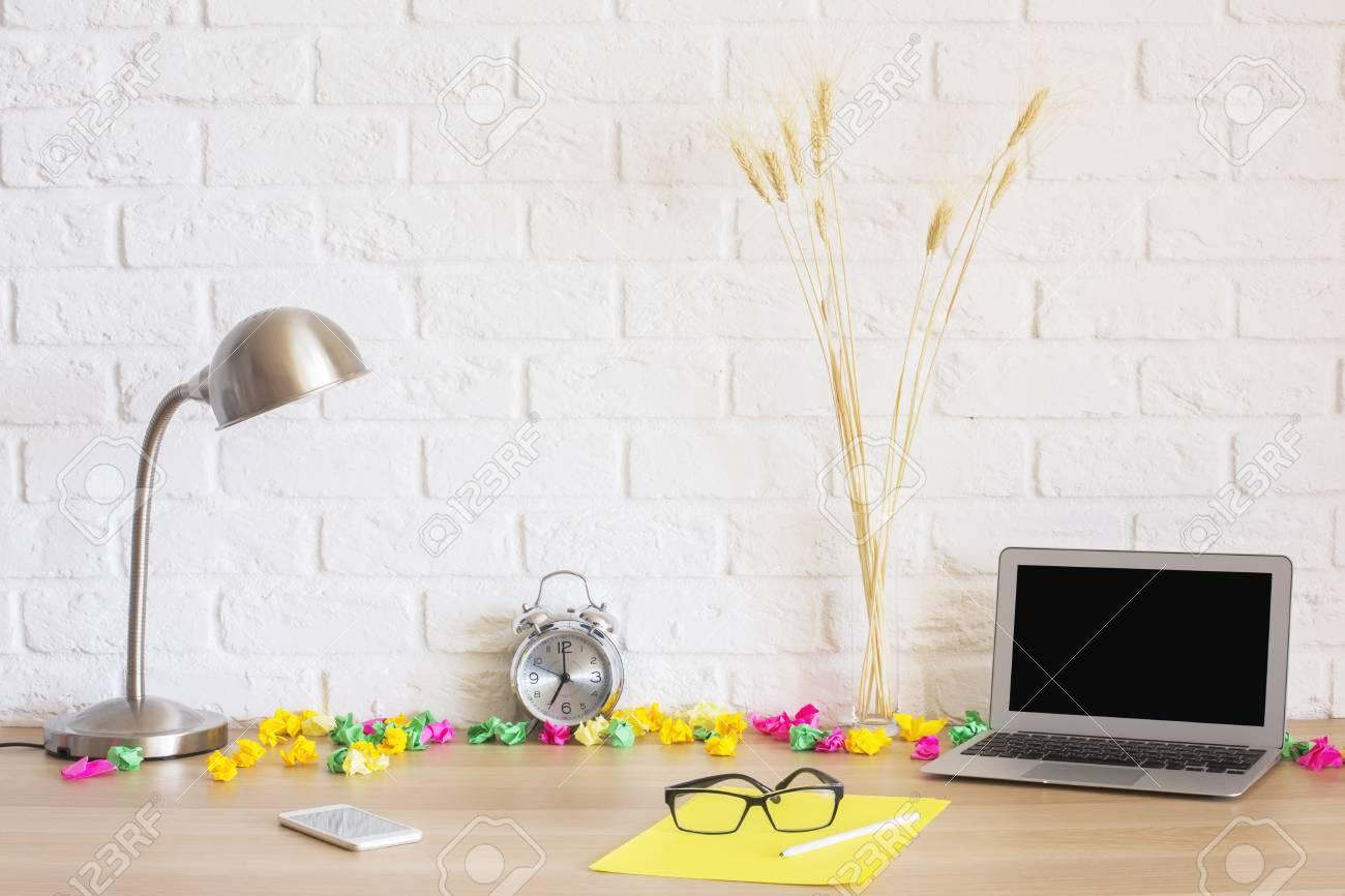 Creative bureau en désordre avec un ordinateur portable blanc