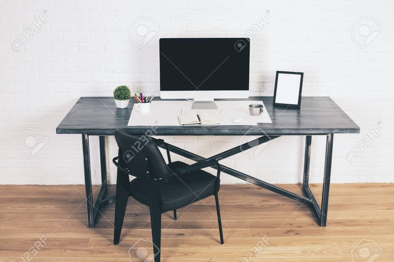 Chaise noire à côté du bureau de concepteur avec lécran vide d