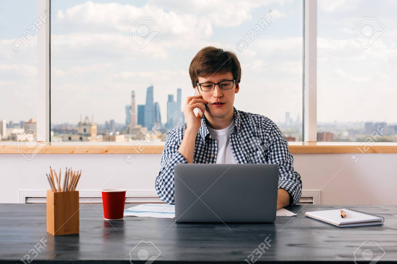 european cup office coffee. Handsome European Man Having Mobile Phone Conversation At Office Desk With Laptop, Business Report, Cup Coffee E