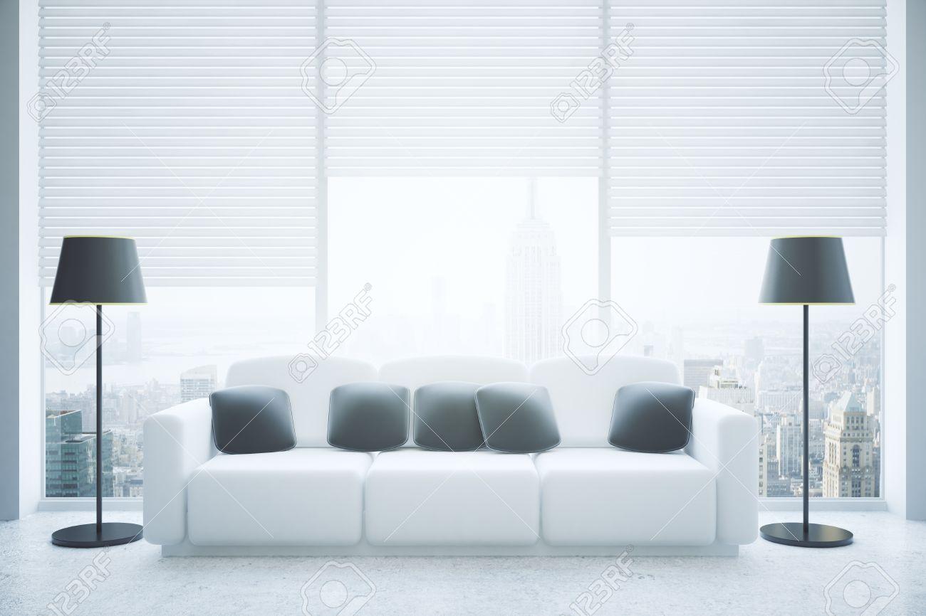 Frontansicht Des Modernen Wohnzimmer Innenraum Mit Schwarzen Kissen Auf  Weißen Couch, Stehlampen, Betonboden Und