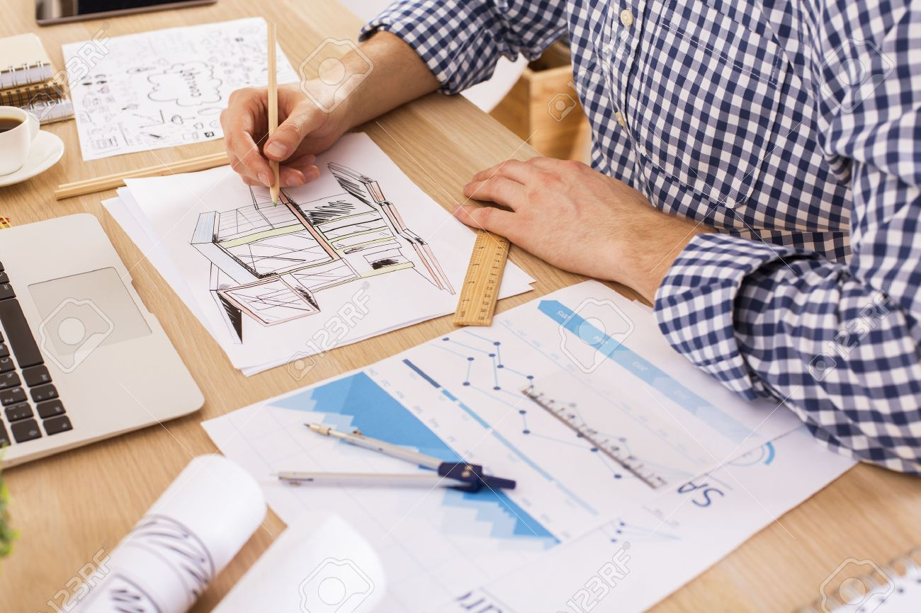 Side view of architect using ruler and pencil to draw blueprint side view of architect using ruler and pencil to draw blueprint on wooden office desktop with malvernweather Choice Image