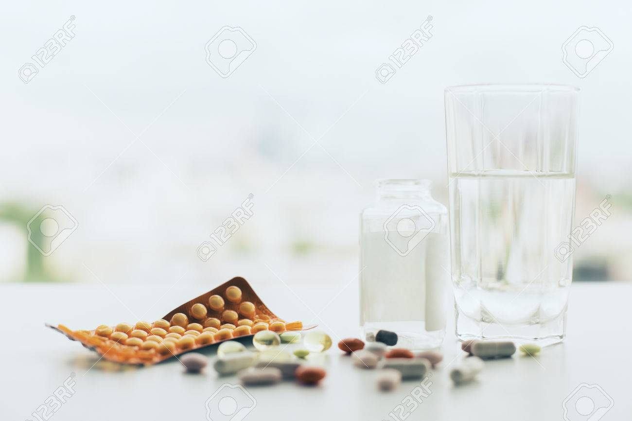 Closeup of white tabletop with different pills, glass of water, medicine bottle and package Standard-Bild - 59959531