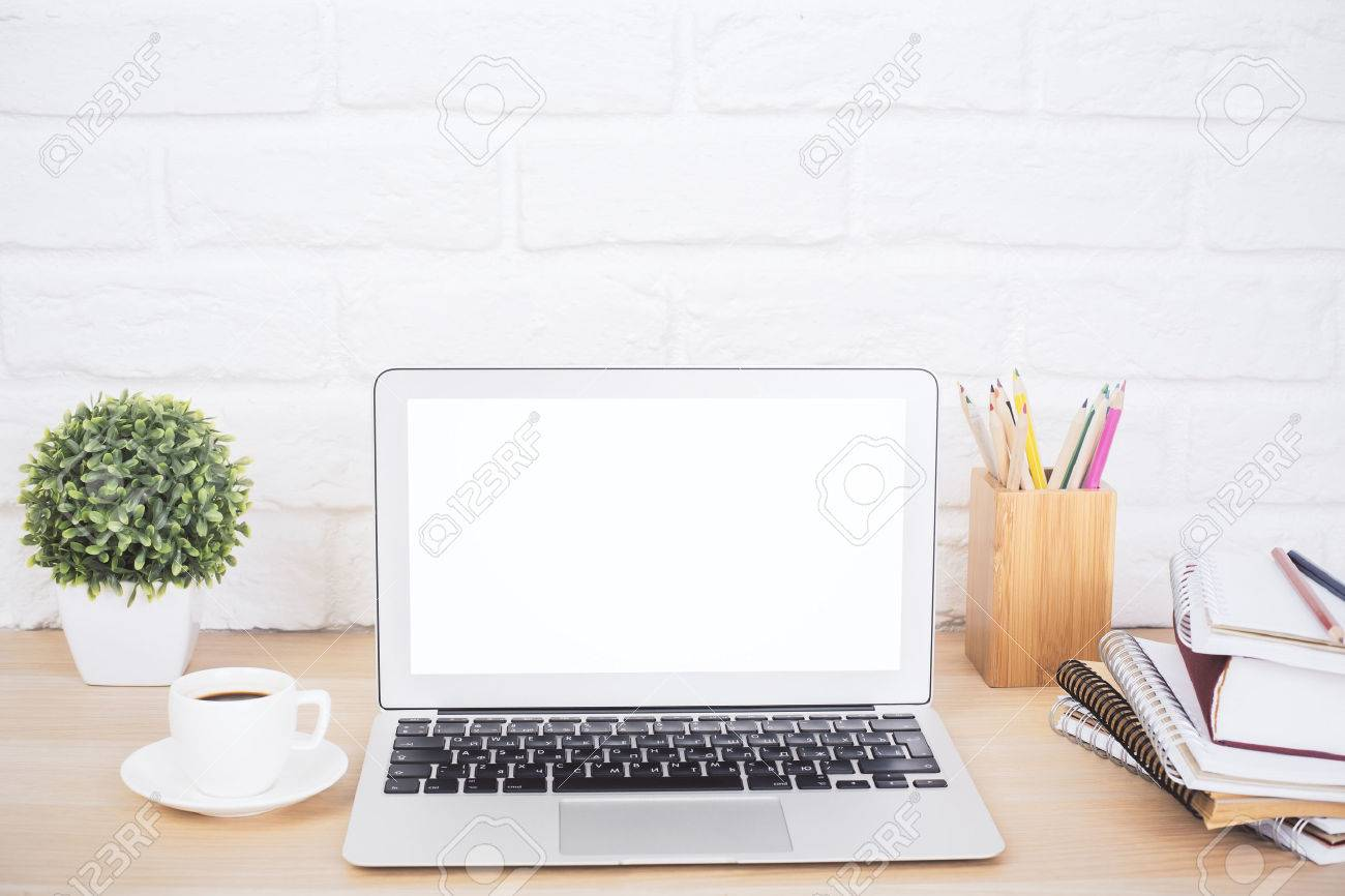 Closeup of creative hipster desktop with blank white laptop, coffee cup and other stationery and decorative items on brick background. Mock up Standard-Bild - 60743002
