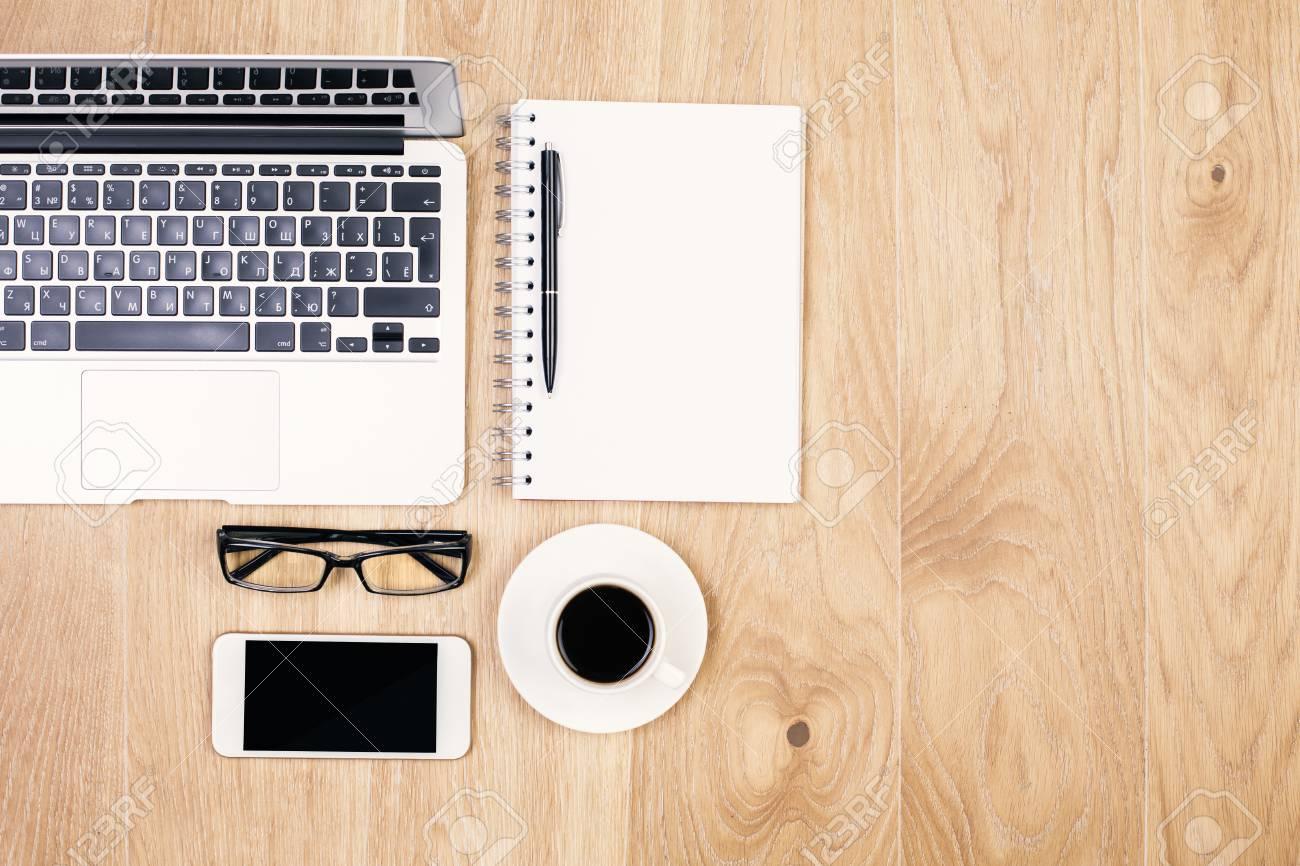 Vue de dessus du bureau en bois clair avec smartphone blanc tasse à
