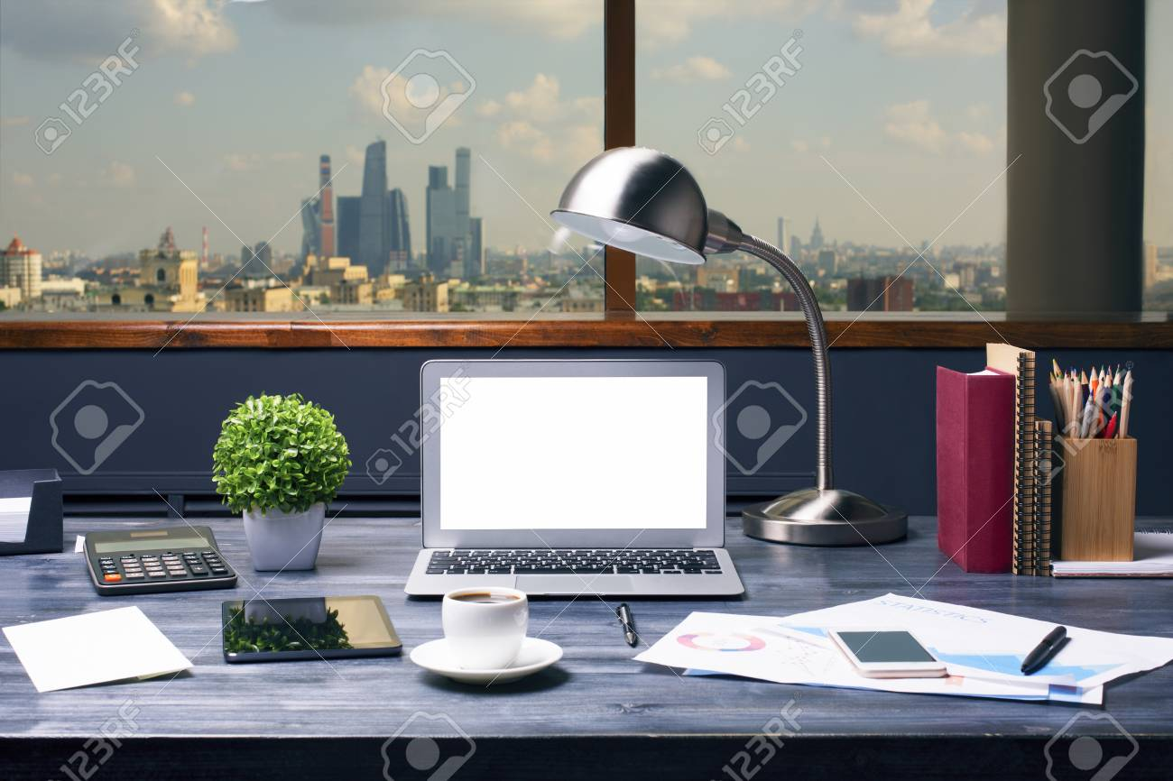 Creative Designer Desktop With Blank White Laptop Computer, Table Lamp,  Plant, Coffee Cup
