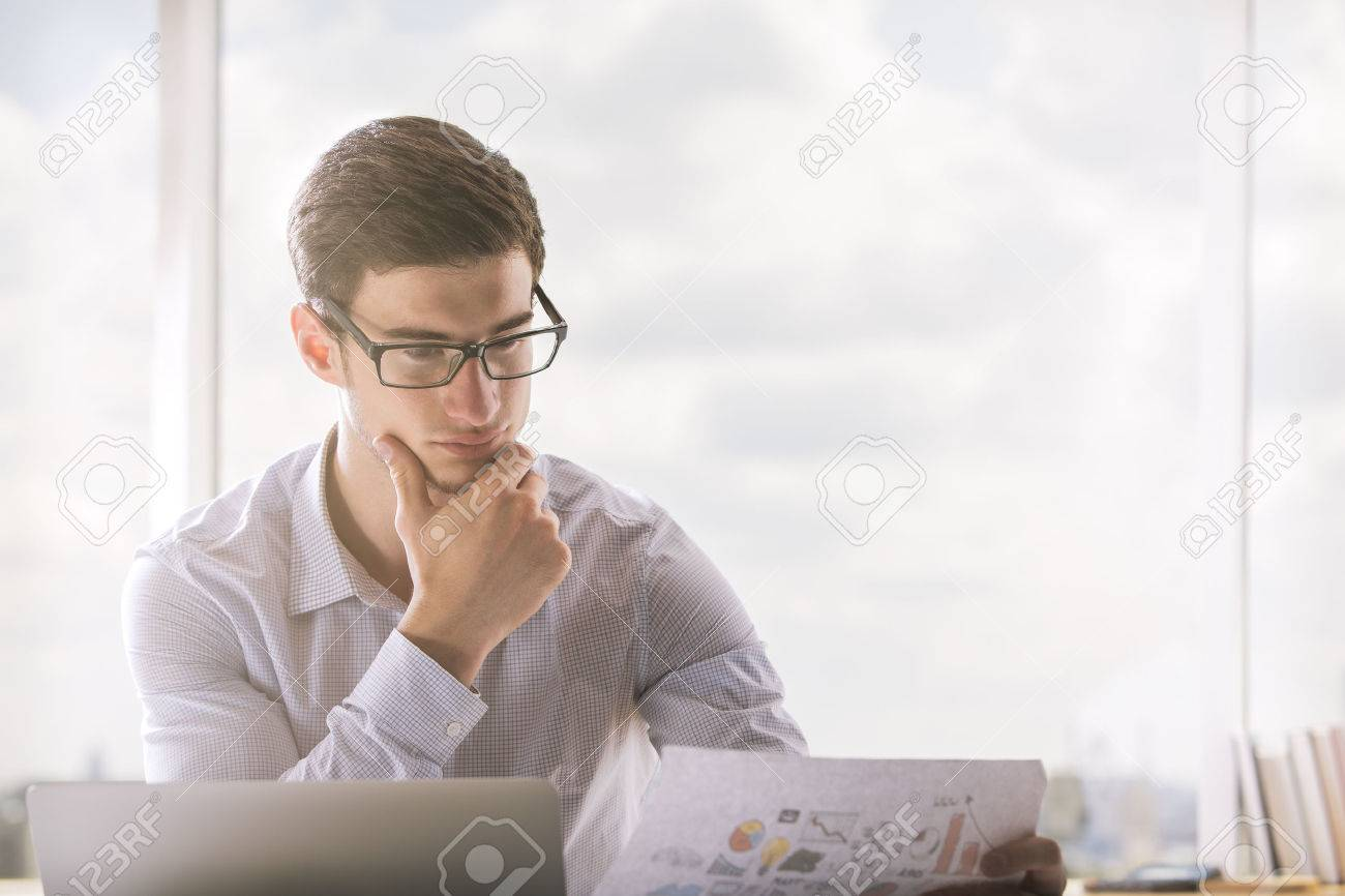 Young businessman in glasses reading documentation in bright office Standard-Bild - 62004912