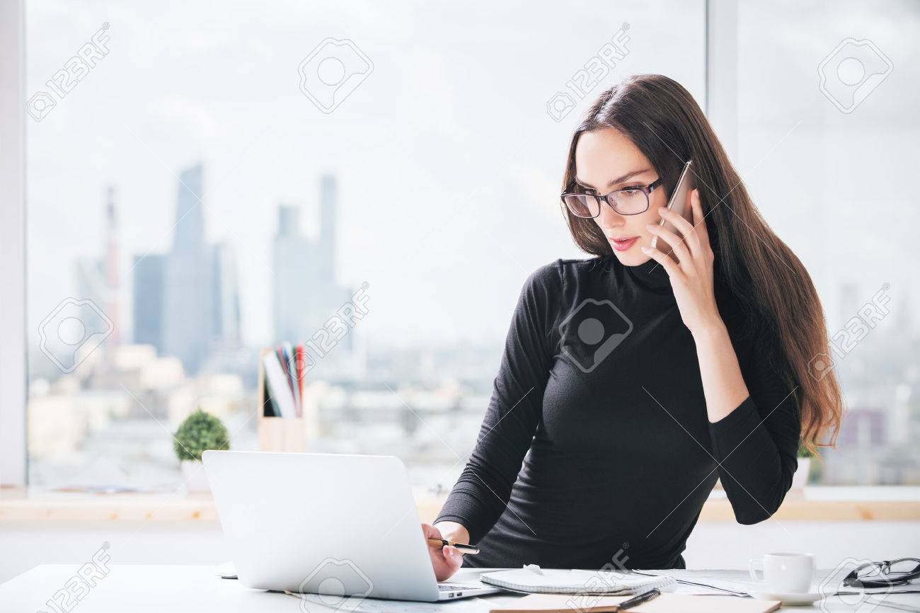 Portrait of charming european businesslady at office desk talking on cellular phone and using laptop computer. Blurry city view in the background Standard-Bild - 62004901
