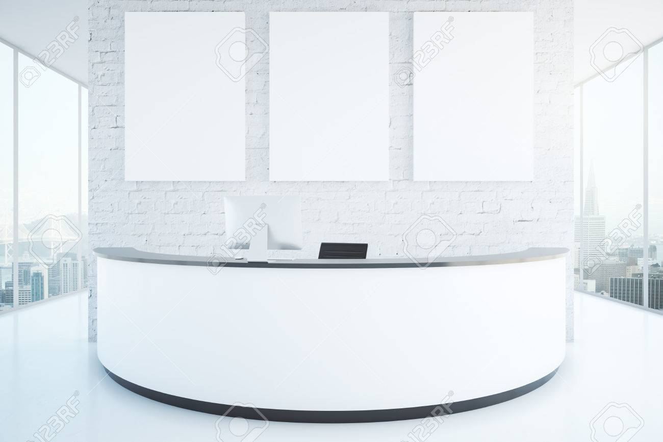 Modern white reception desk with three blank posters in interior..