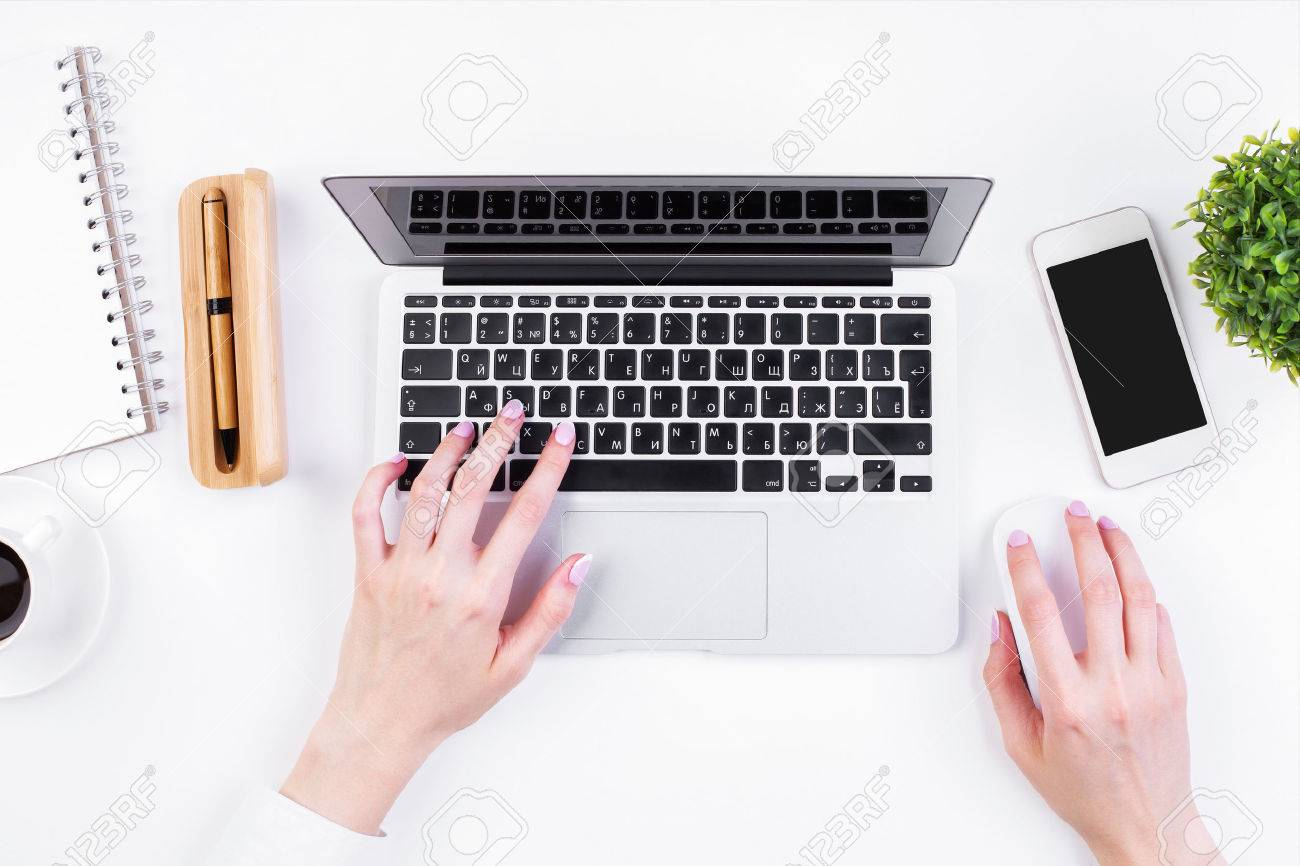 Top view of girl's hands typing on laptop keypad placed on white office desktop with blank smartphone, coffee cup, decorative plant and supplies. Mock up Standard-Bild - 63392096