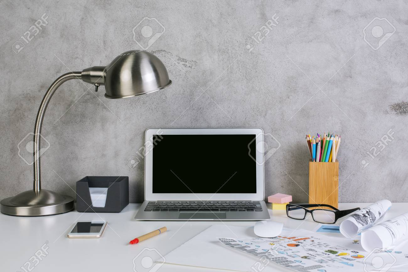 Front View Of Creative Workplace With Blank Laptop Display, Table Lamp,  Supplies, Business