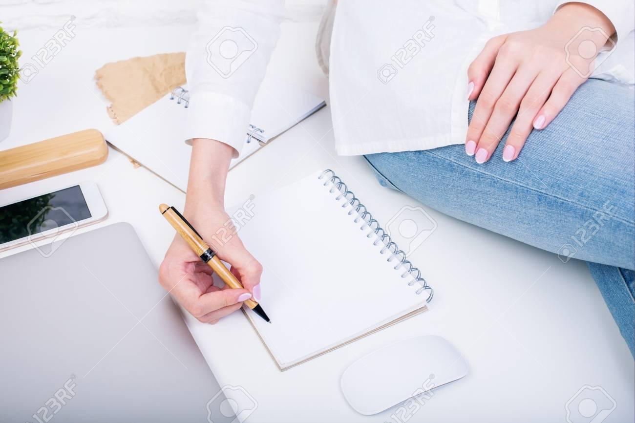 Gros plan de femme assise sur un bureau blanc avec un ordinateur