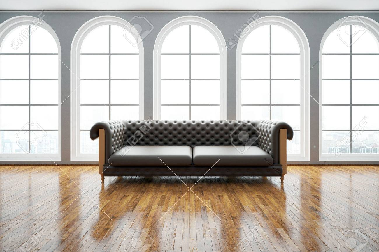 Front view of dark leather sofa in bright room with wooden floor..