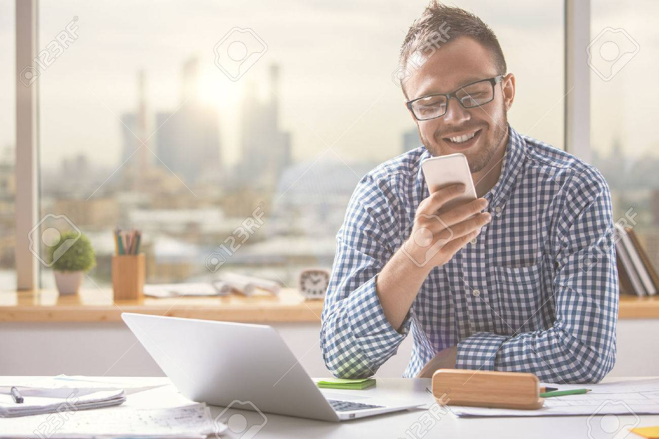Portrait of handsome european man using cellphone while sitting at office table with laptop computer and other items Standard-Bild - 64315302