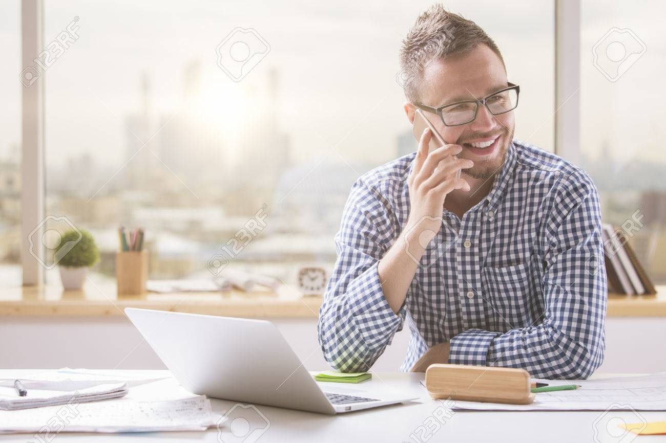 Portrait of handsome young man in glasses sitting at office desk with laptop computer and talking on mobile phone. Communication concept Standard-Bild - 65094753