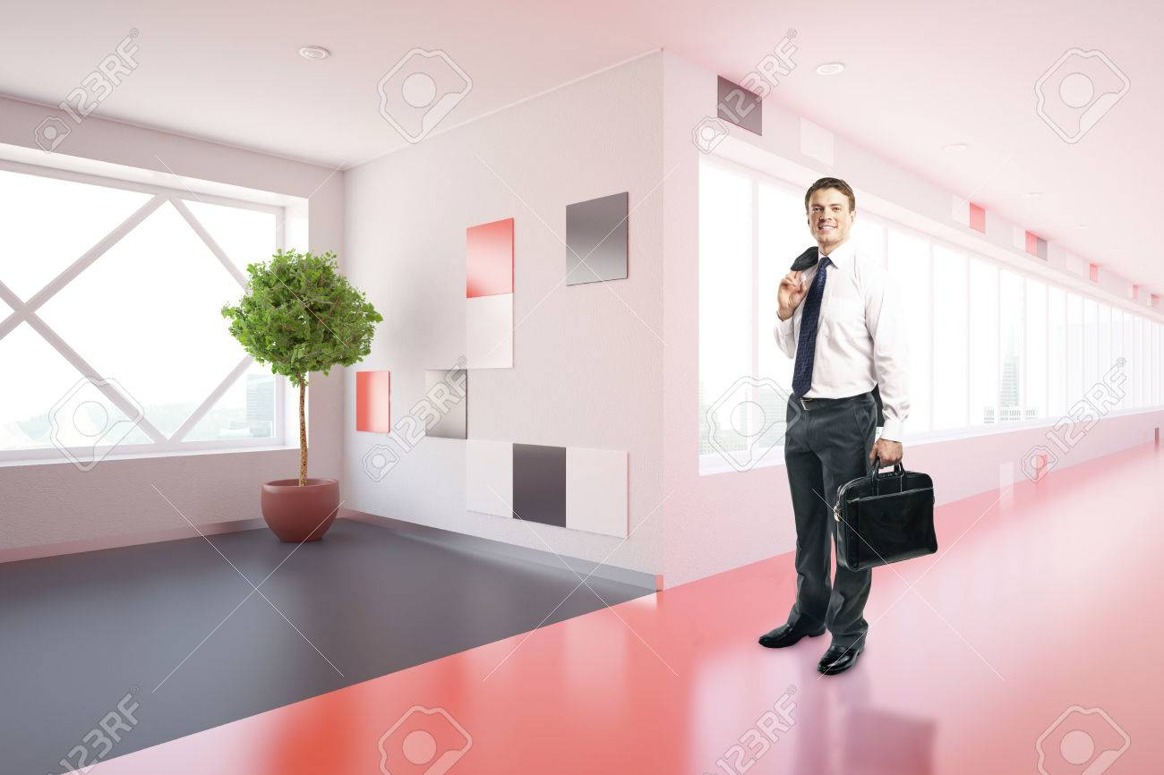 Side view of smiling young businessman in modern red corridor