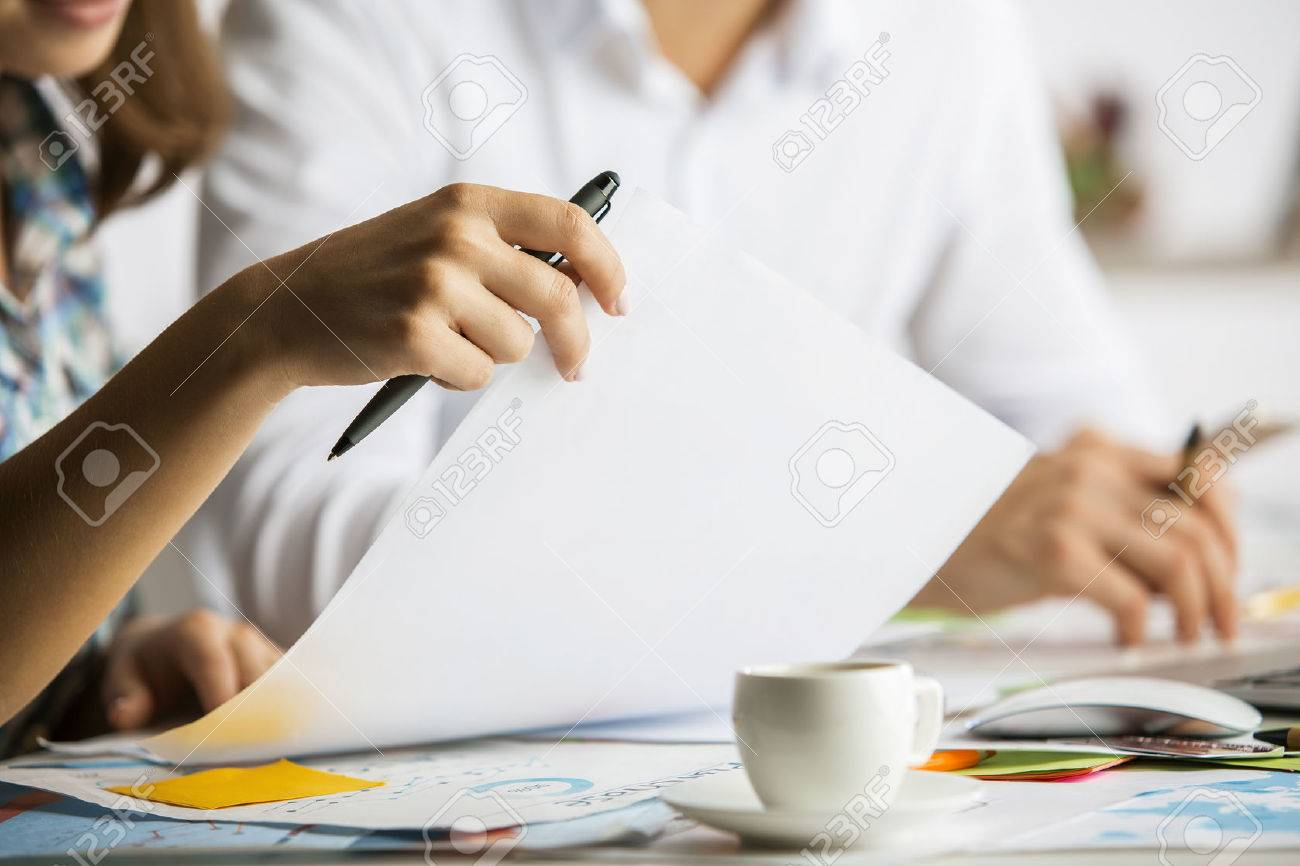 Close up of caucasian man and woman doing paperwork on messy table with coffee cup. Teamwork concept Standard-Bild - 65980512