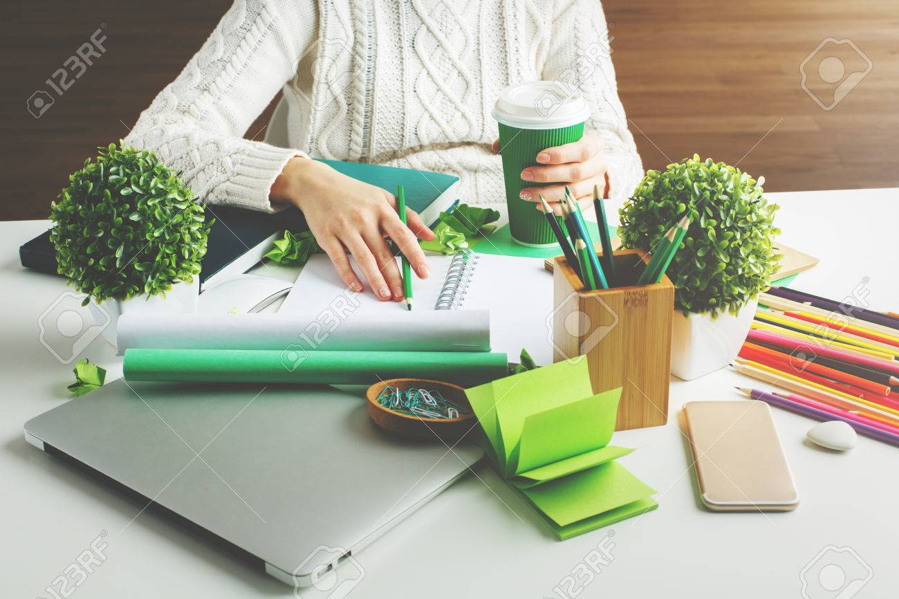 Girl hodling green coffee cup and writing in spiral notepad placed on creative desktop with various items Standard-Bild - 66534285