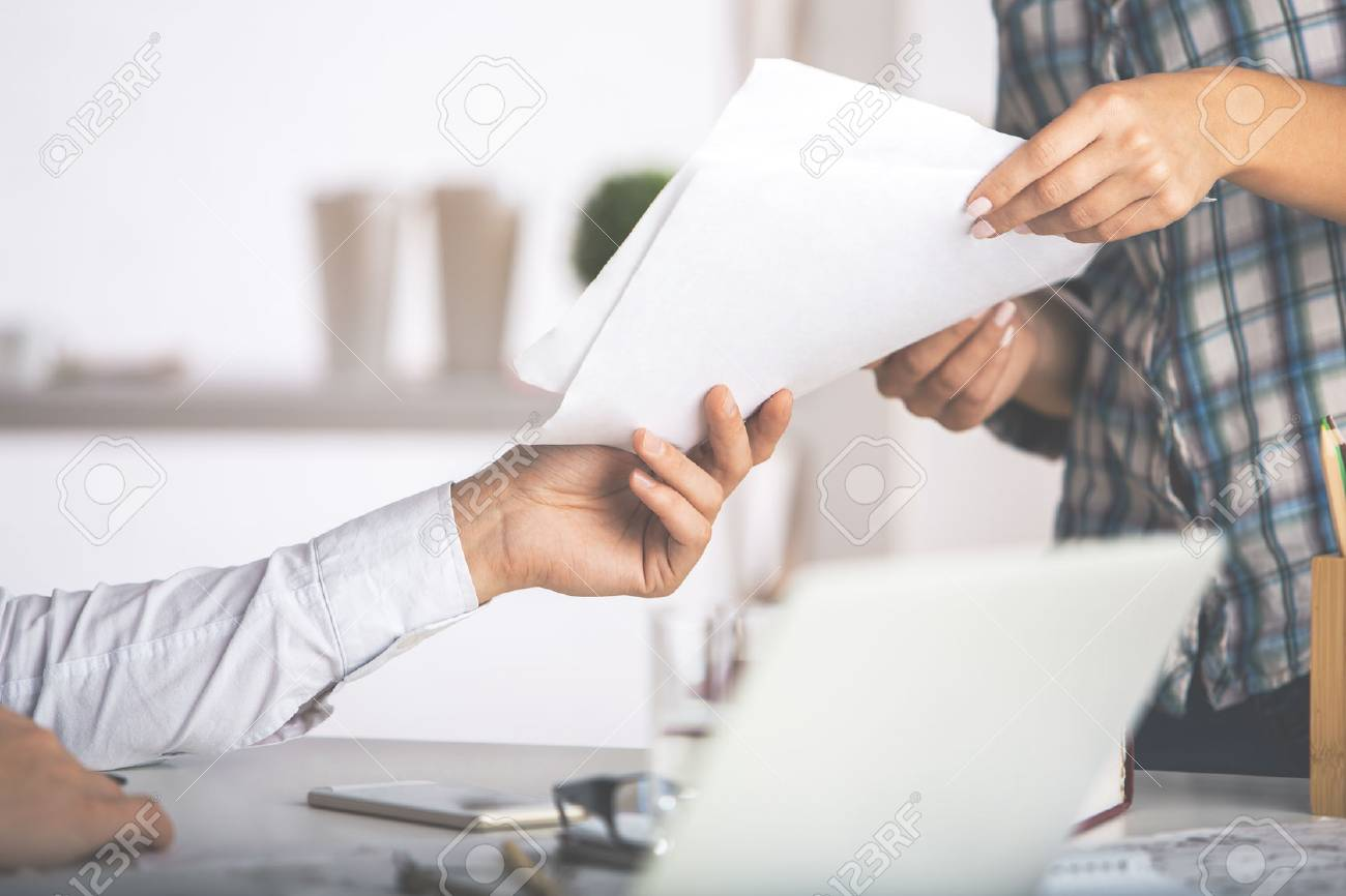 Close up of caucasian man and woman handing documents to each other. Teamwork concept Standard-Bild - 66601827