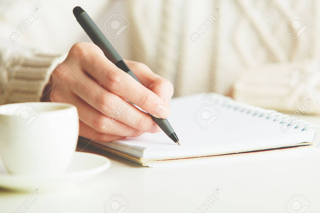 Woman writing in spiral notepad placed on bright desktop with coffee cup. Education concept Standard-Bild - 66487135