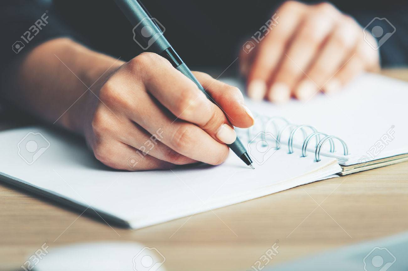 Close up of woman's hands writing in spiral notepad placed on wooden desktop with various items Standard-Bild - 66544771
