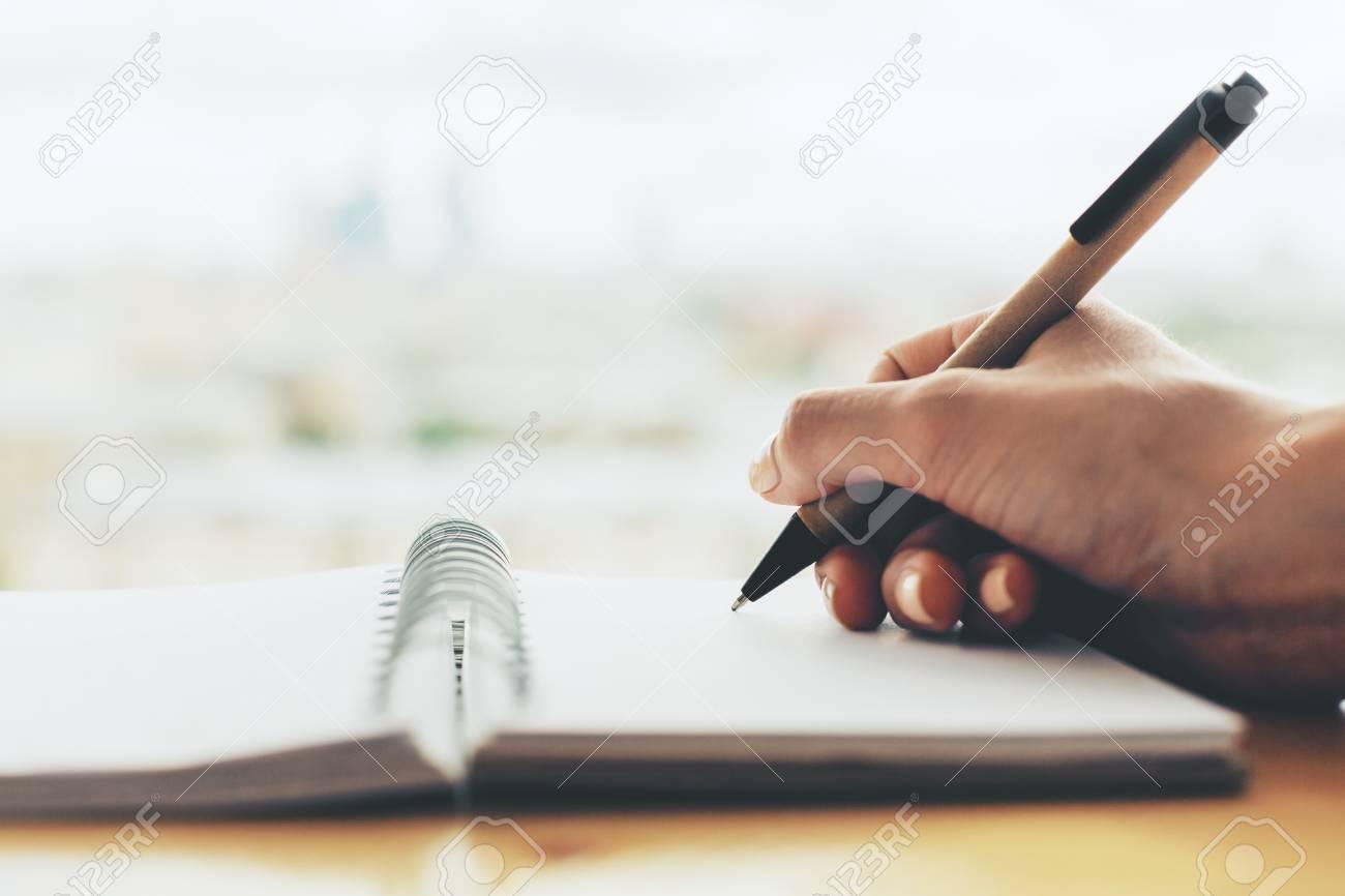 Fille écrit dans le bloc notes en spirale placé sur le bureau en