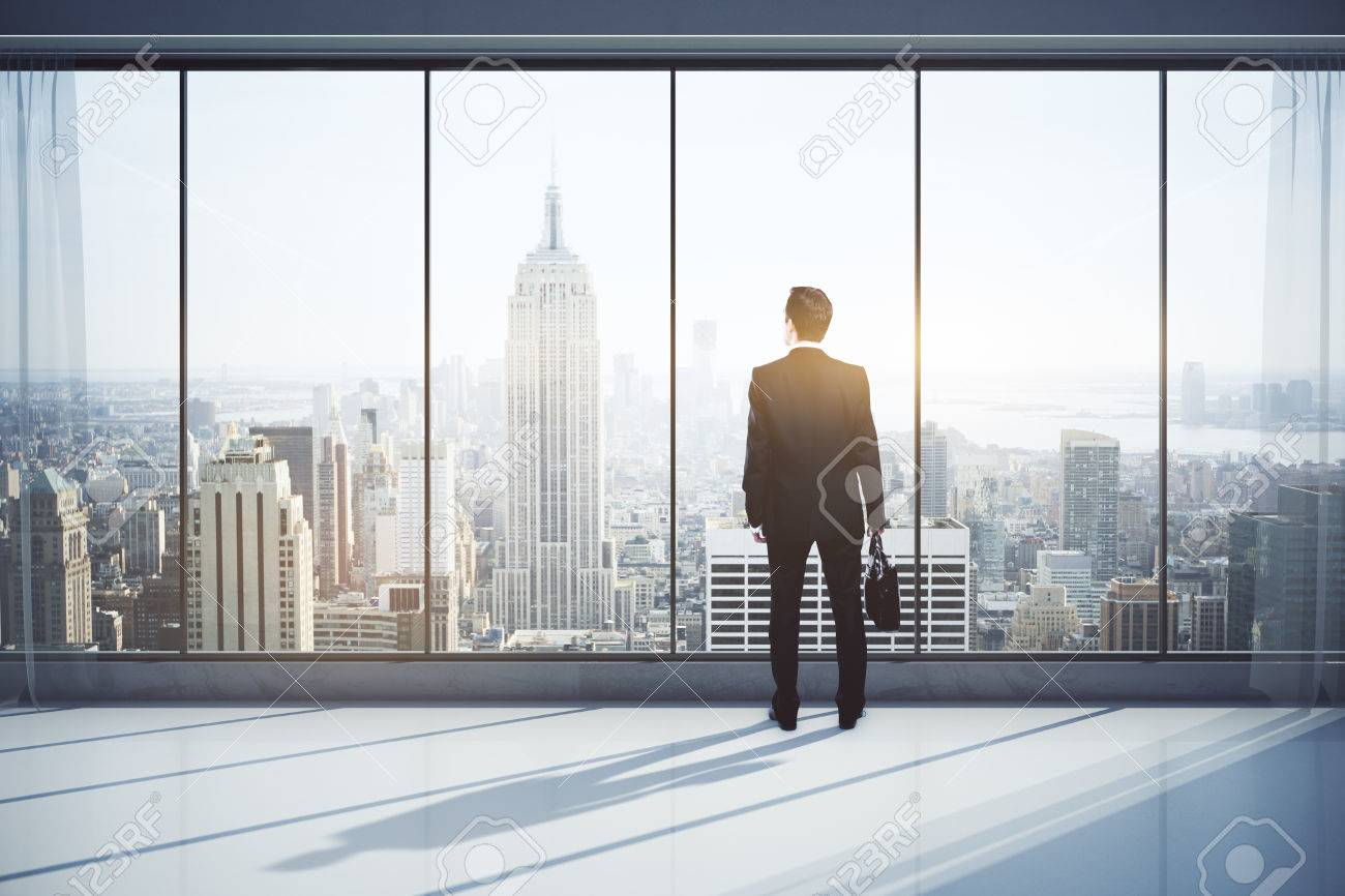 Back view of man with briefcase in modern interior with city view, looking into the distance. Research concept. 3D Rendering Standard-Bild - 69360080