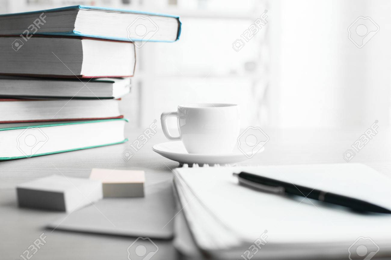 Outstanding Close Up Of Office Desktop With Pile Of Books Coffee Cup And Interior Design Ideas Clesiryabchikinfo
