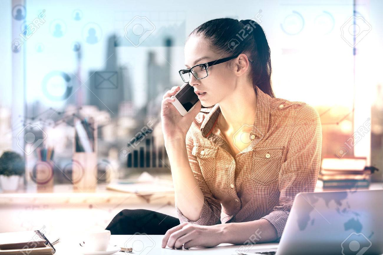 Attractive caucasian woman at workpace with abstract business charts talking on the phone and working on project. Finance concept. Toned image Standard-Bild - 71339207