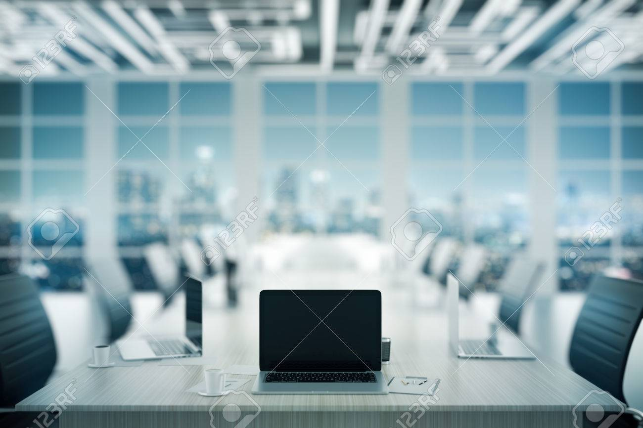 Close up of blank laptop placed on wooden conference table in dark interior. Mock up, 3D Rendering. Meeting concept Standard-Bild - 71670429