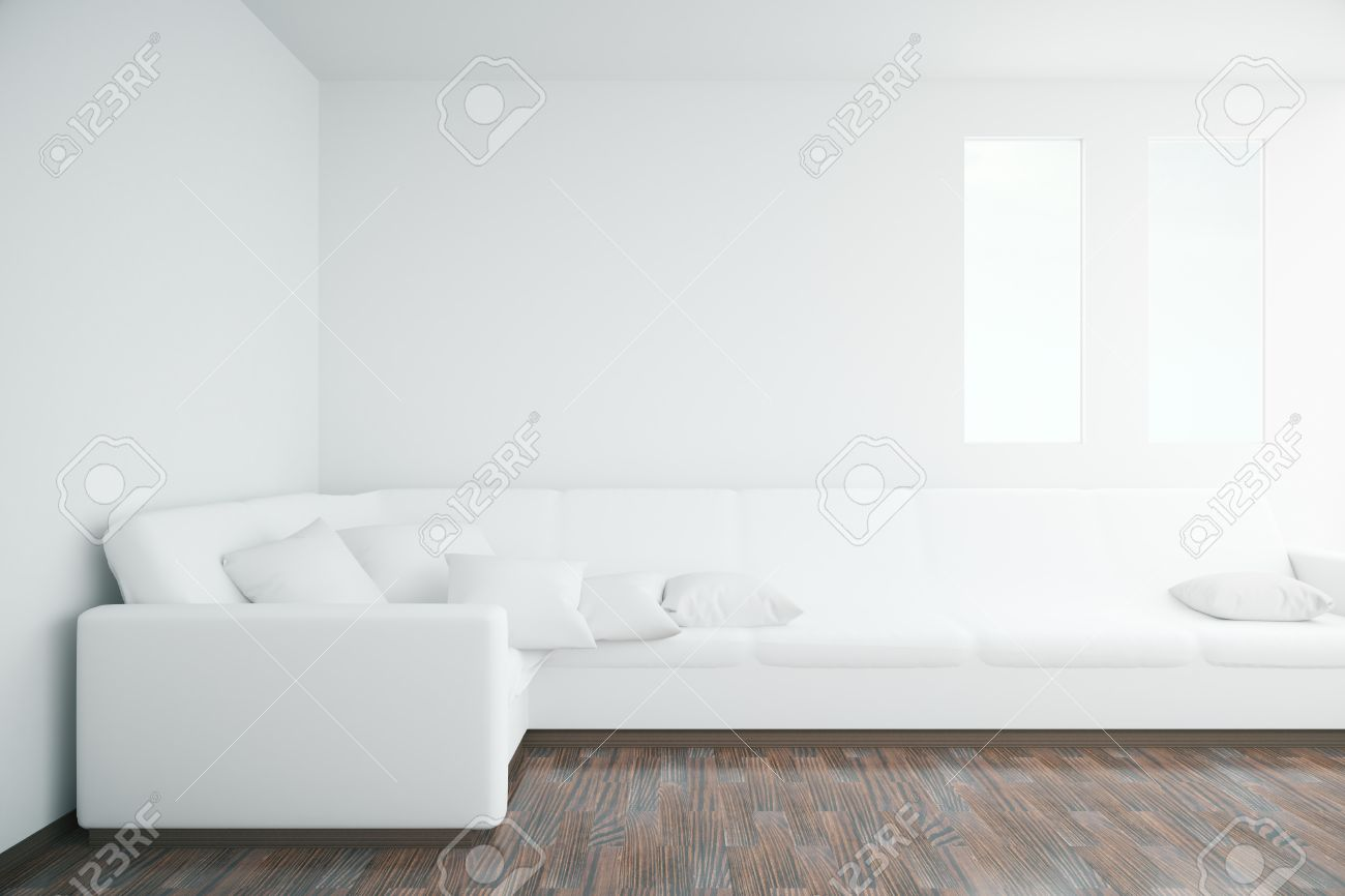 White Interior With Large Sofa Windows Wooden Floor And Blank Wall Mock Up