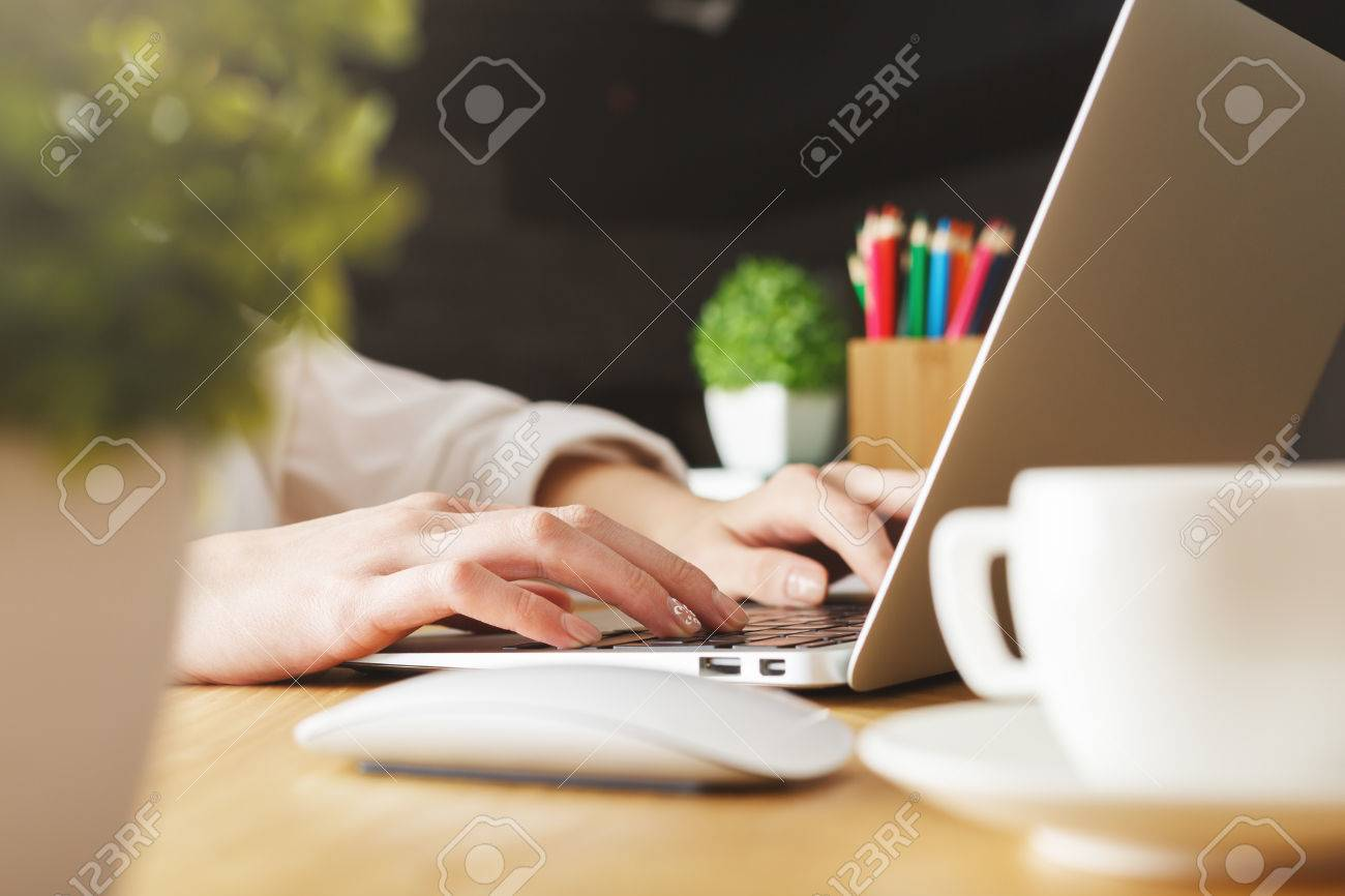 Close up and side view of female hands typing on laptop keyboard placed on wooden desktop with decorative plants and coffee cup Standard-Bild - 73769296