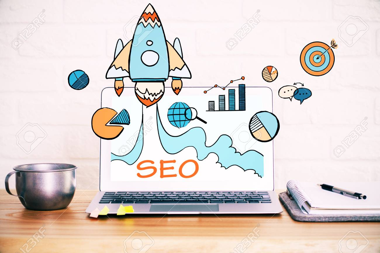 Close up of creative designer desktop with SEO spaceship hologram on laptop screen, coffe cup and other items on white brick wall background. Startup and web concept - 87605064