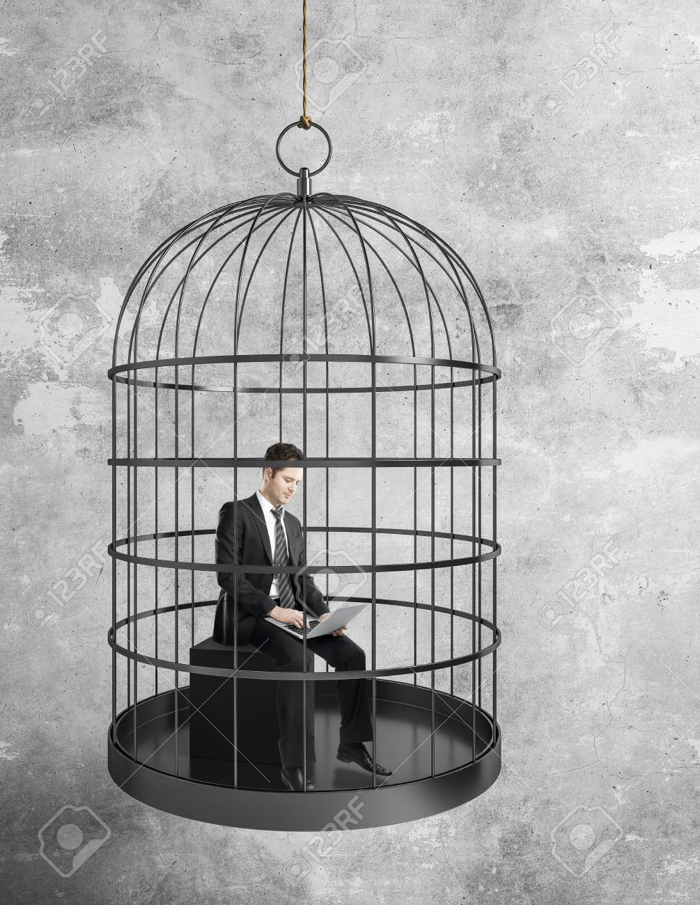 businessman working hard with laptop in birdcage on concrete wall background. Freedom and innovation concept - 104891560