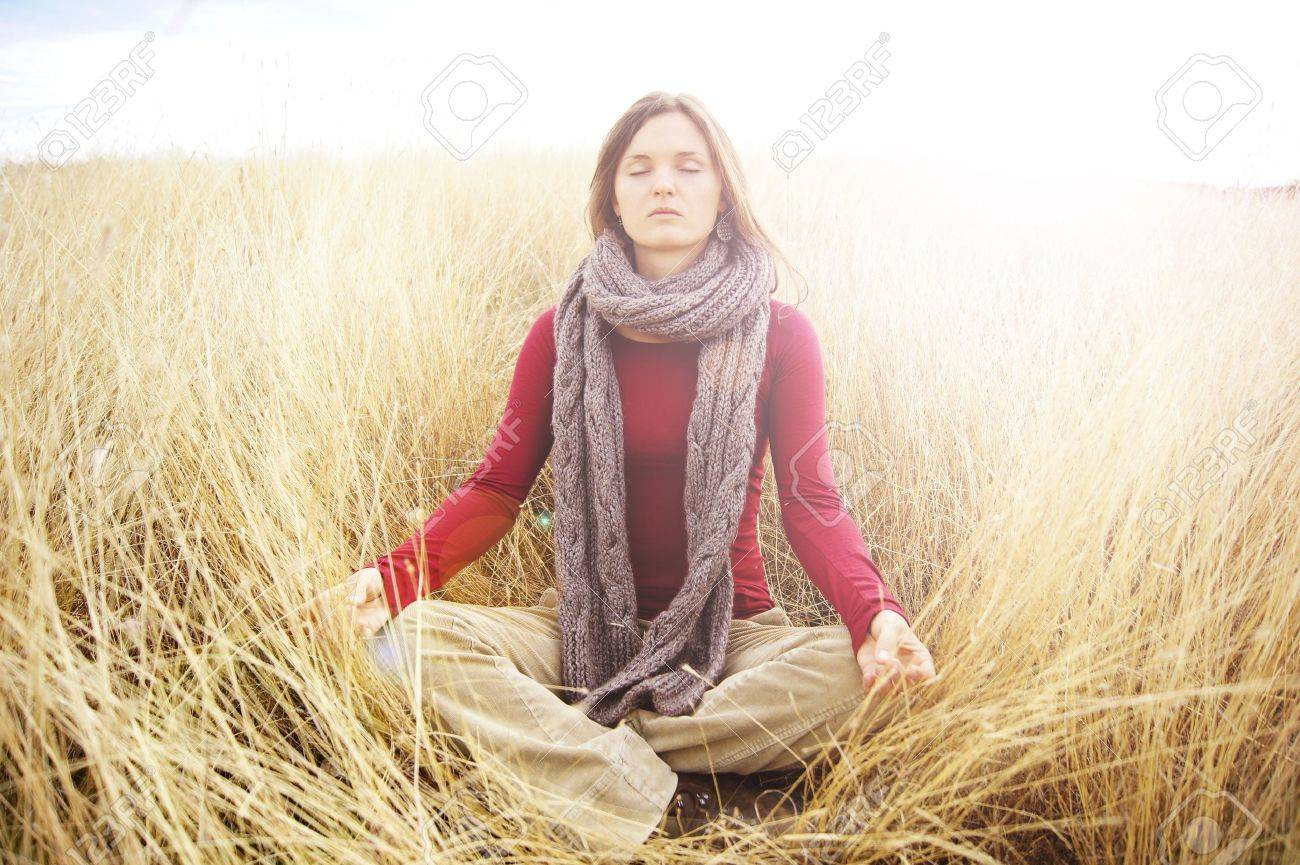 Beautiful young woman meditating in a open field in the long autumn grass Stock Photo - 10967906