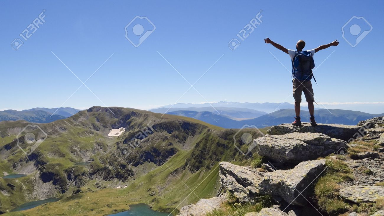 Male hiker in Rila mountains, Bulgaria, with arms stretched out to enjoy the mountain scenery Stock Photo - 11975146