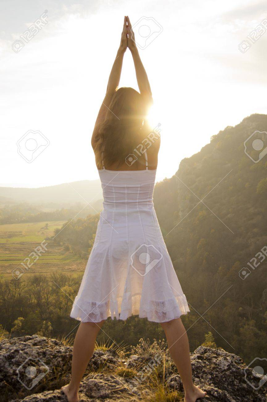 Young woman standing on a rock greeting the light of the sun stock young woman standing on a rock greeting the light of the sun stock photo 12889205 kristyandbryce Images