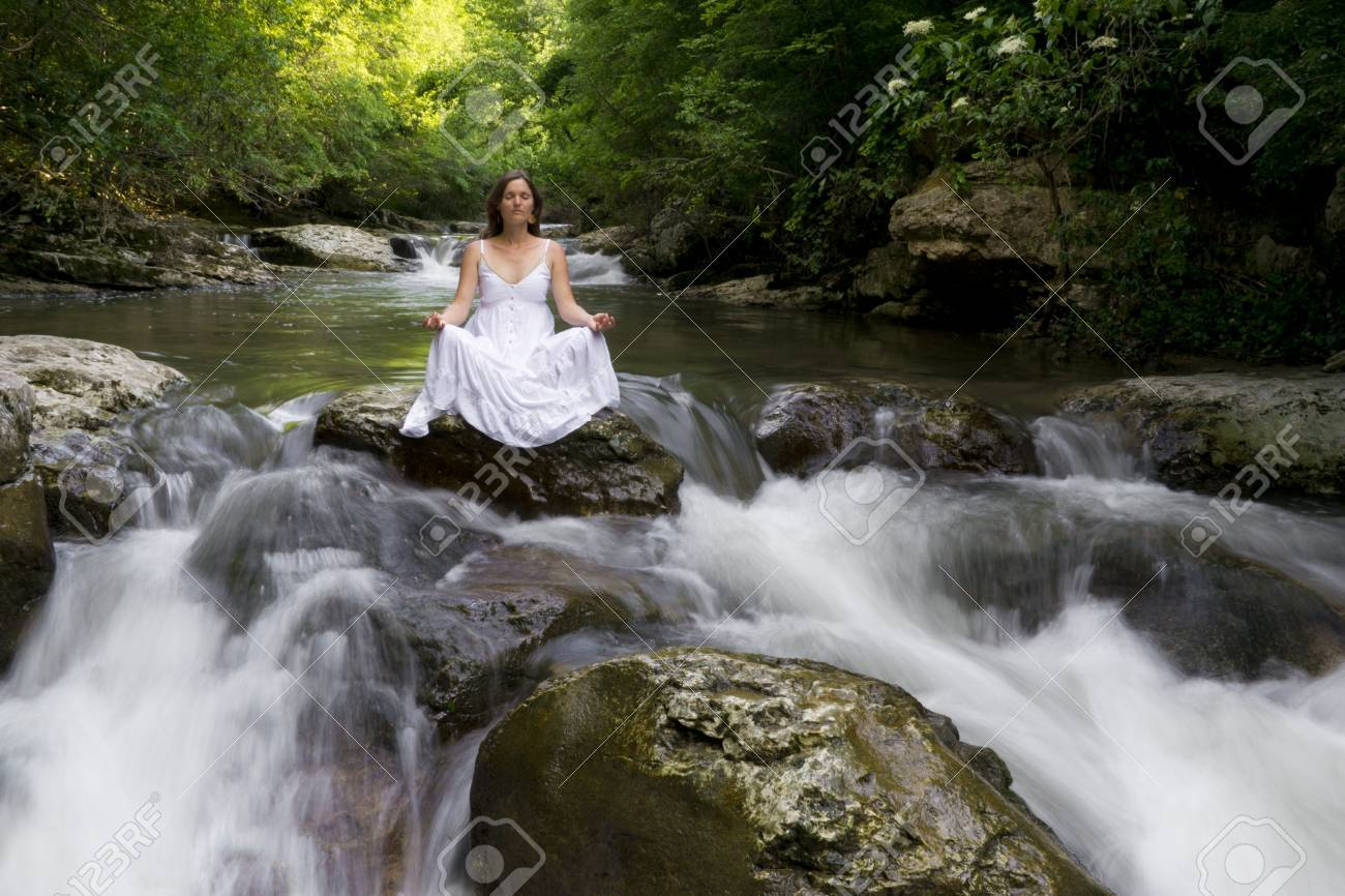 Beautiful young woman meditating surrounded by the purifying waters of a clear mountain stream Stock Photo - 14070665