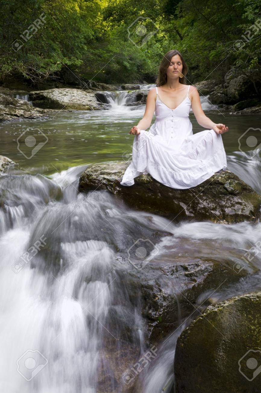 Beautiful young woman meditating surrounded by the purifying waters of a clear mountain stream Stock Photo - 14070647