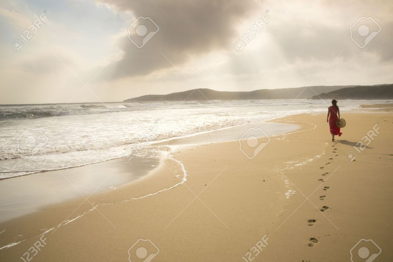 Young woman walk on an empty wild beach towards celestial beams of light falling from the sky Stock Photo - 14786922