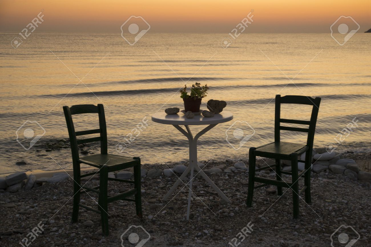 Due sedie vuote e un tavolo in piedi solo nel sole pacifico di una ...