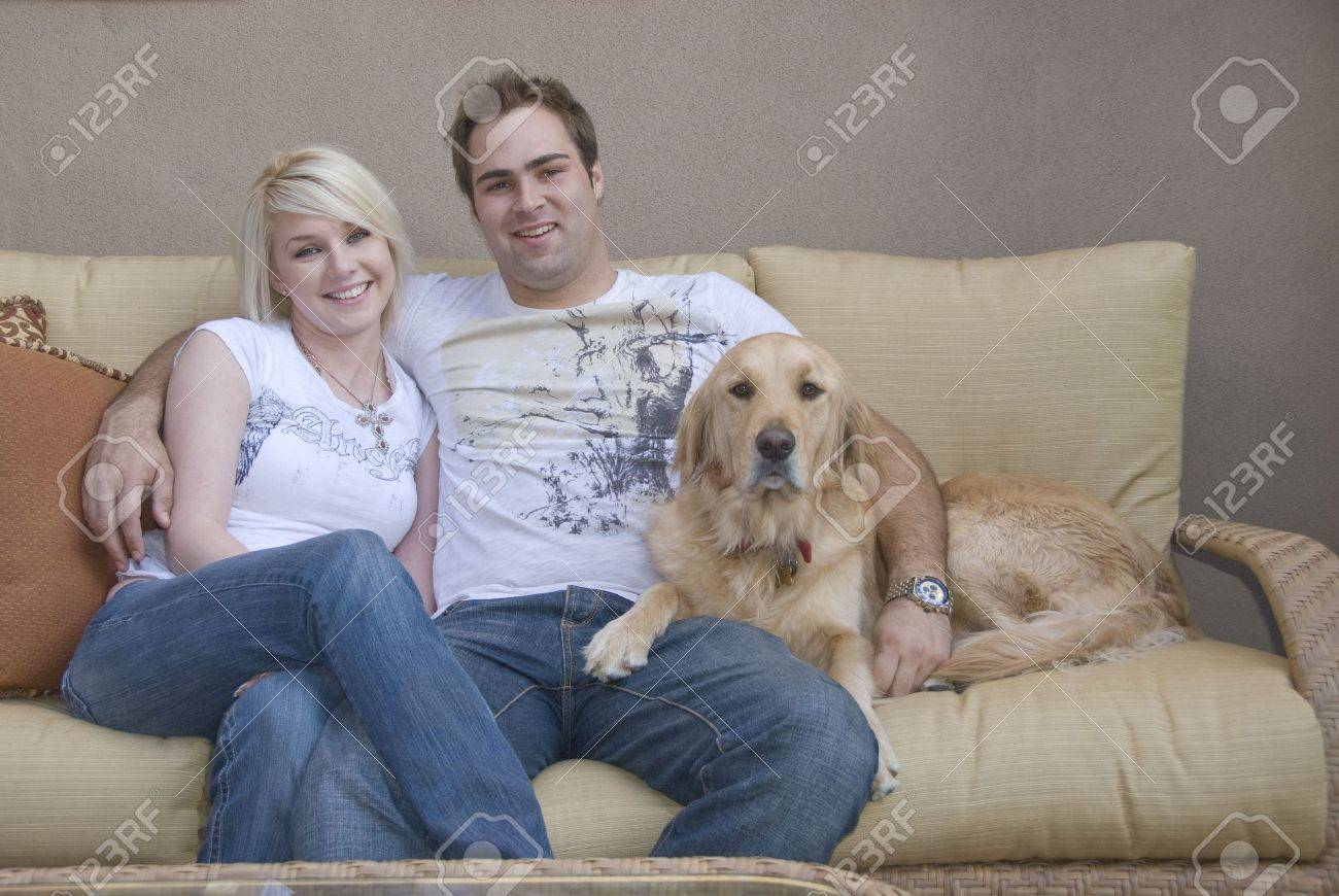 Attractive Young Couple And Their Golden Retriever Dog Sitting