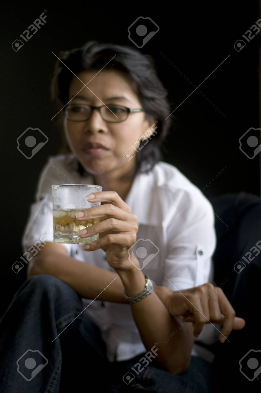 dark portrait of a woman holding an alcoholic drink Stock Photo - 3564462