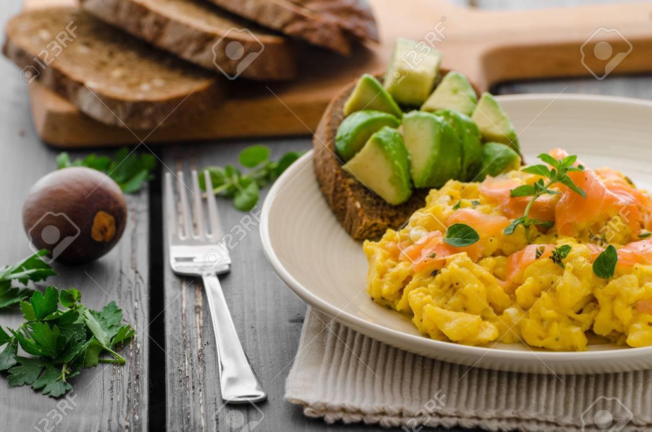 Scrambled Eggs With Smoked Salmon And Whole Wheat Toast Avocado Lemon Stock Photo